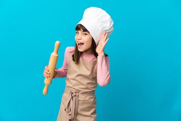 Petite fille tenant un rouleau à pâtisserie isolé sur bleu en écoutant quelque chose en mettant la main sur l'oreille