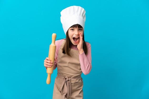 Petite fille tenant un rouleau à pâtisserie isolé sur fond bleu avec une expression faciale surprise et choquée