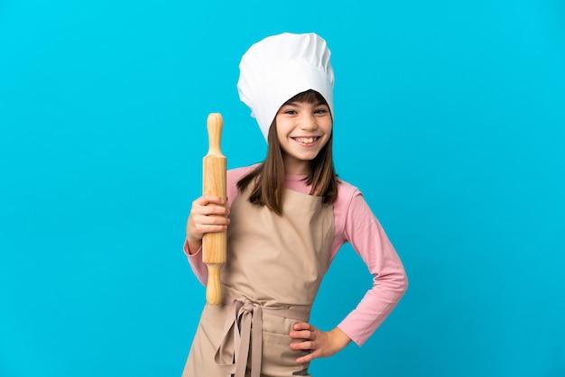 Petite fille tenant un rouleau à pâtisserie isolé sur fond bleu posant avec les bras à la hanche et souriant