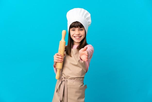 Petite fille tenant un rouleau à pâtisserie isolé sur fond bleu se serrant la main pour conclure une bonne affaire