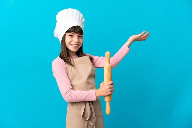 Petite fille tenant un rouleau à pâtisserie isolé