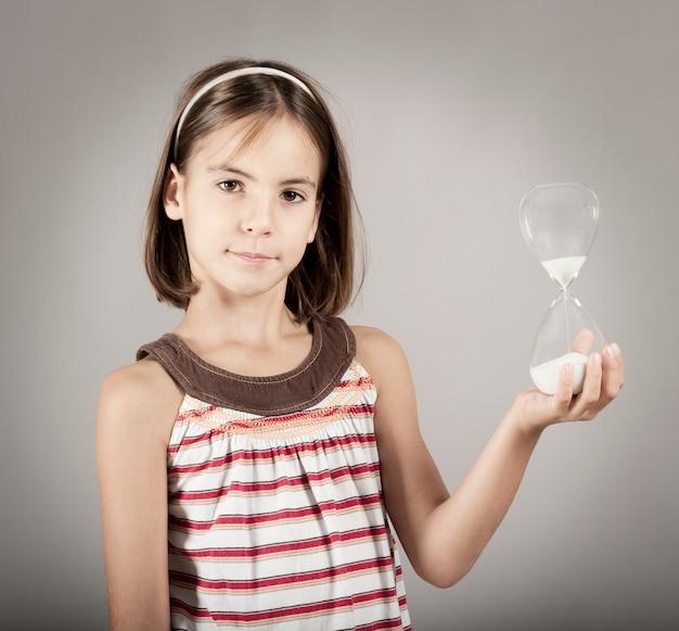 Petite fille tenant un sablier