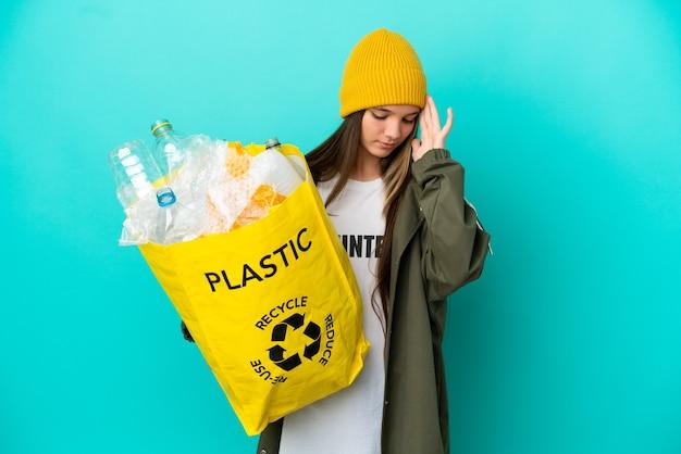Petite fille tenant un sac plein de bouteilles en plastique à recycler sur fond bleu isolé avec maux de tête
