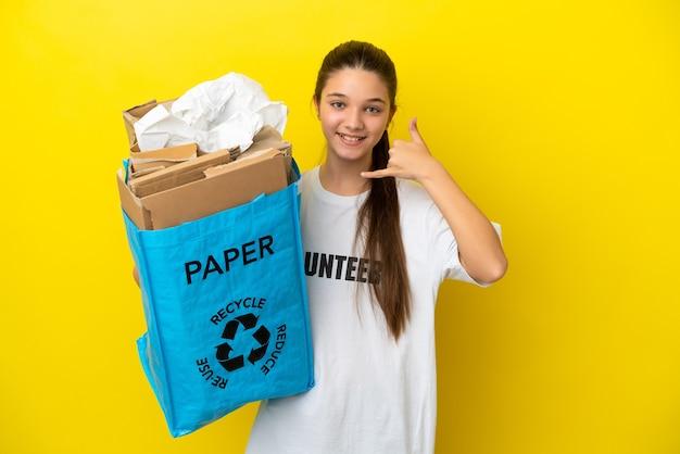Petite fille tenant un sac de recyclage plein de papier à recycler sur fond jaune isolé faisant un geste de téléphone. rappelle-moi signe