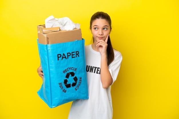 Petite Fille Tenant Un Sac De Recyclage Plein De Papier à Recycler Sur Fond Jaune Isolé En Pensant à Une Idée Tout En Levant Les Yeux Photo Premium