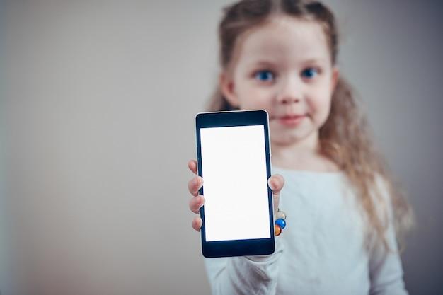 Petite fille tenant un smartphone avec un écran blanc