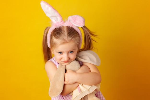 Petite fille tenant son jouet lapin contre le mur jaune