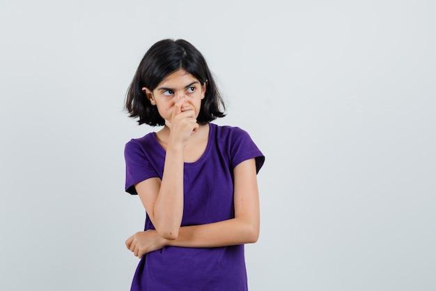 Petite fille tenant son menton en t-shirt et à la pensif.