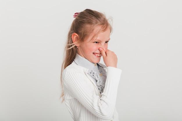 Petite fille tenant son nez