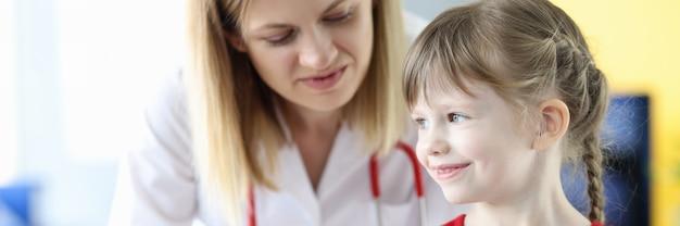 Petite fille tenant un téléphone portable dans le bureau des médecins. notion de pédiatrie