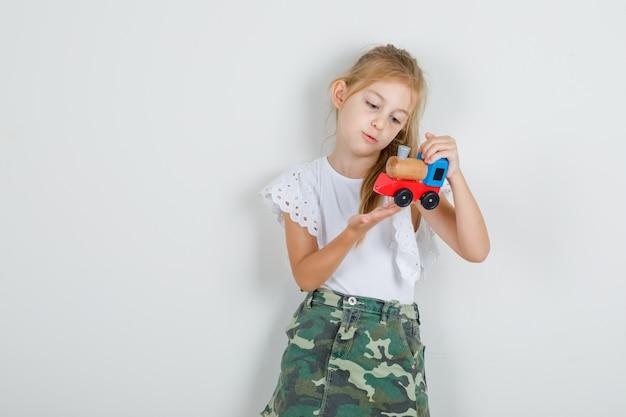 Petite fille tenant un train jouet en t-shirt blanc