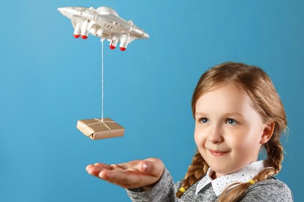 Une petite fille tend la main vers une boîte emballée attachée à un quadricoptère.