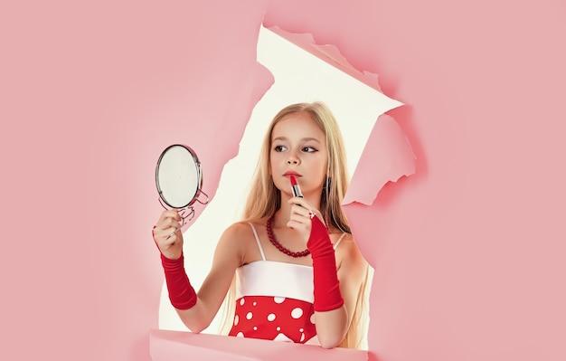 Petite fille tenir le rouge à lèvres. petit adolescent sur fond rose. kid avec du maquillage.