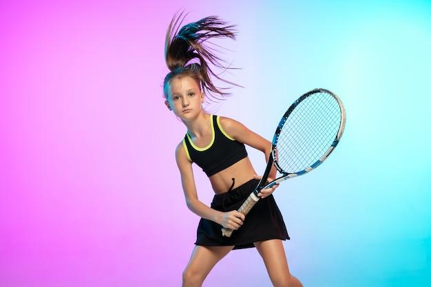 Petite fille de tennis en tenue de sport noire isolée sur un mur dégradé à la lumière du néon