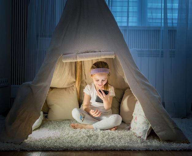 Petite fille en tente tipi dans la chambre