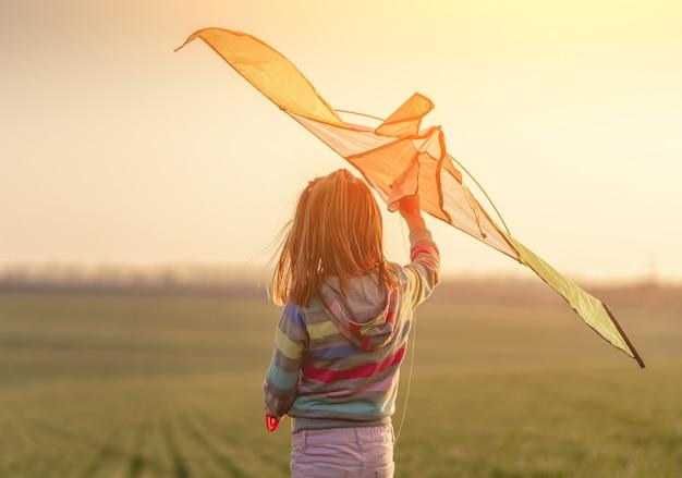 Petite fille, tenue, cerf volant, à, coucher soleil