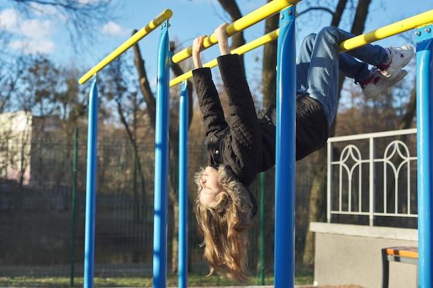 Petite fille la tête en bas sur une aire de jeux de sports en plein air avec les yeux fermés, profitant de la chaleur et de la lumière du soleil, premier soleil du printemps, vitamine d