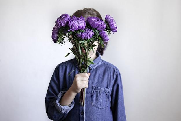 Une petite fille tient un bouquet de chrysanthèmes bleus dans ses mains.