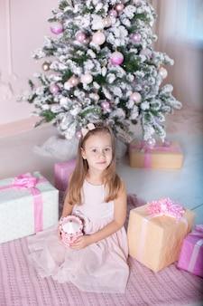Petite fille tient le carrousel de jouets musicaux près de l'arbre de noël