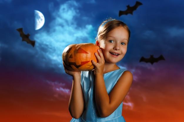 Petite fille tient une citrouille sur le fond du ciel lunaire du soir.