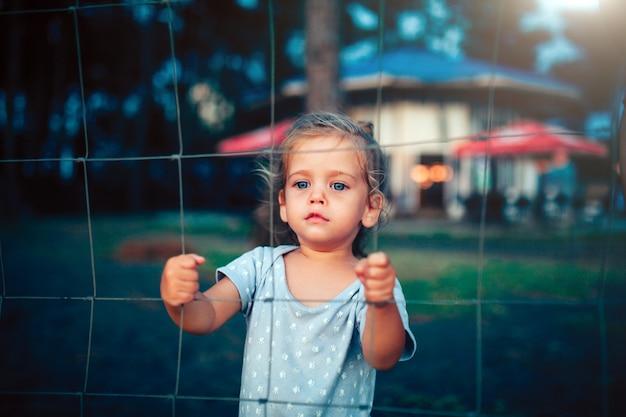 La petite fille tient la clôture à deux mains et regarde la caméra à travers la grille