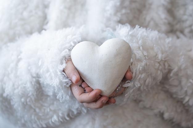 Une petite fille tient un cœur blanc dans ses mains.