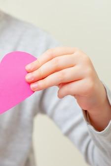 Petite fille tient coeur rose.