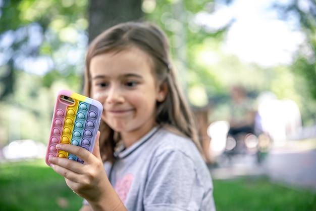 Une petite fille tient dans sa main un téléphone dans un étui à picots, un jouet anti-stress tendance.