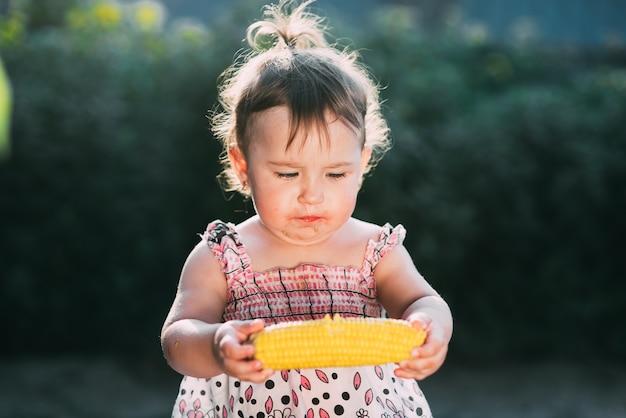 Une petite fille tient du maïs bouilli et pense à manger ou non