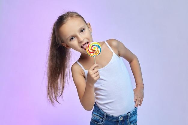 Une petite fille tient un gros bonbon