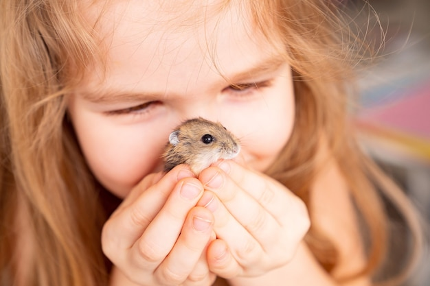 Une petite fille tient un hamster sur son visage. l'amitié des enfants avec les animaux domestiques