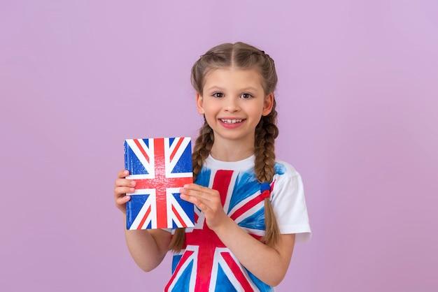 Une petite fille tient un manuel d'anglais dans ses mains.