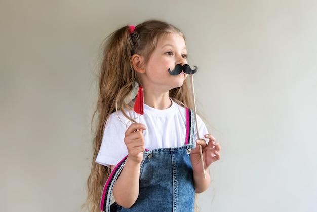 Une petite fille tient une moustache mascarade dans une main et un bonbon à sucer dans l'autre