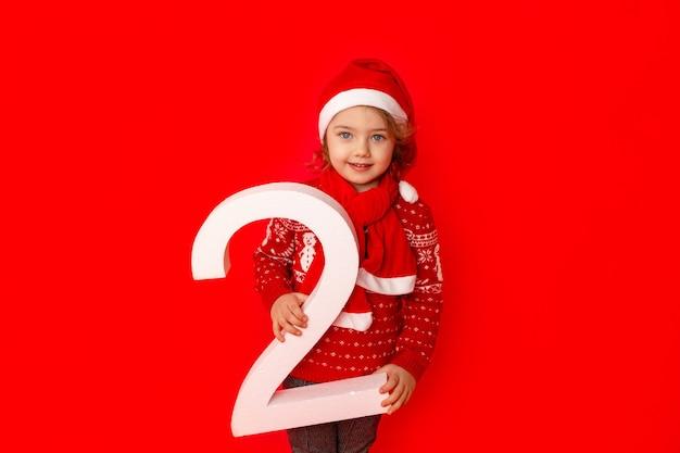 Une petite fille tient le numéro deux dans le chapeau du père noël sur fond rouge, espace pour le texte