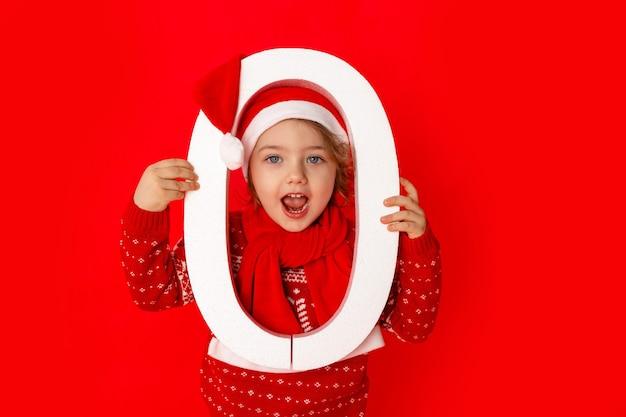 Une petite fille tient le numéro zéro dans le chapeau du père noël sur fond rouge, espace pour le texte