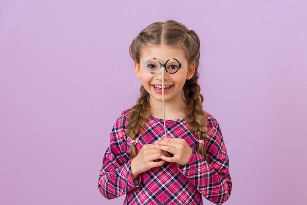 Une petite fille tient une paire de lunettes de déguisement près de son visage.