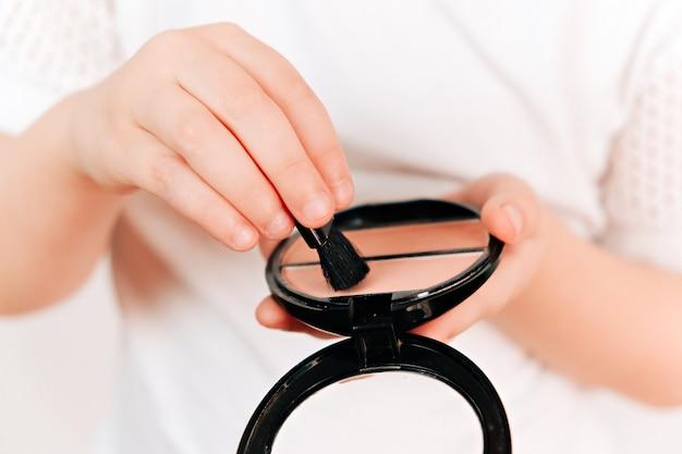 Petite fille tient la palette. concept de maquillage