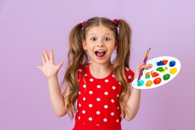 Une petite fille tient une palette de peinture dans ses mains et est très heureuse.