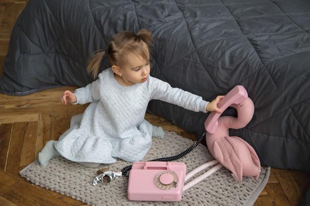 Une petite fille tient le récepteur d'un vieux téléphone fixe rose. l'enfant laisse le flamant rose parler au téléphone. l'enfant a décidé de manger une barre granola.