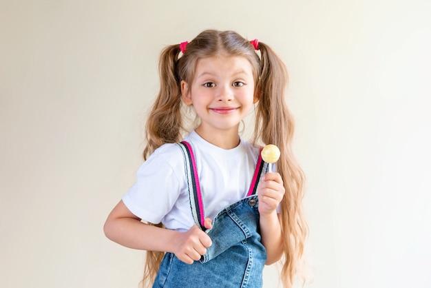 Une petite fille tient une sucette à la main.