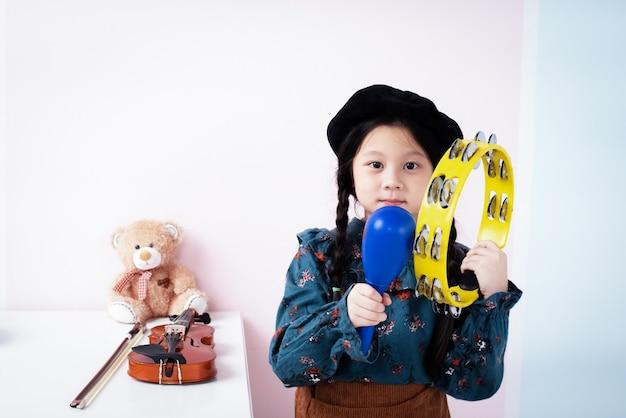 La petite fille tient un tambourin et des maracas à la main avec un sentiment de joie