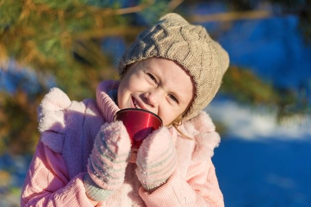 Petite fille tient une tasse de thé chaud dans la forêt d'hiver. enfance heureuse. enfants à l'extérieur concept de vacances d'hiver amusant