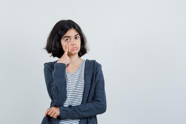 Petite fille tirant sa paupière par le doigt en t-shirt