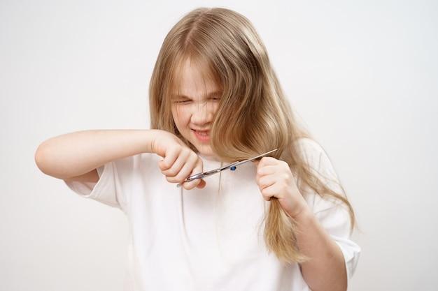 La petite fille tond ses longs cheveux avec des ciseaux sur blanc.