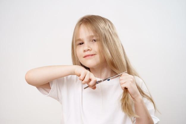 La petite fille tond ses longs cheveux avec des ciseaux sur fond blanc. coupe de cheveux à la mode pour le bébé. coiffeur. les farces des enfants. la coupe de cheveux