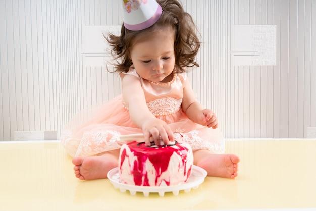 Petite fille touchant son gâteau d'anniversaire avec sa main