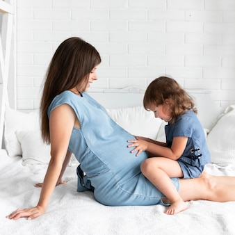 Petite fille touchant le ventre de sa mère