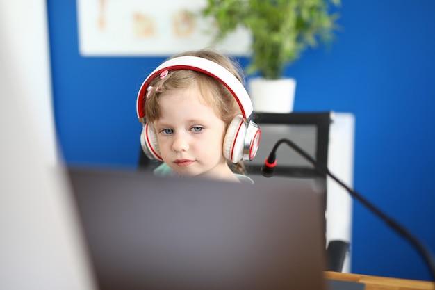 Petite fille travaille avec ordinateur portable sur fond de maison.
