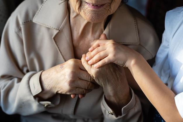 Petite fille et très vieille femme. petit enfant étreignant la grand-mère. petite fille