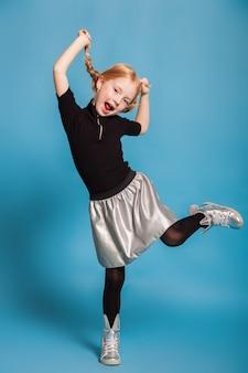 Petite fille avec des tresses dans des vêtements élégants